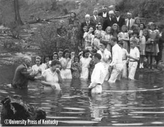 """Baptizings are special events in the lives of mountain people, who have an inherent interest in what follows after their stay here is ended. A fit time to scare the sinful into full repentance for their wrong doin's, as funerals do, baptizings follow protracted revival meetings held by a preacher of homespun origin and scriptural beliefs. Wint """"Preacher"""" Bolton was such a man, a member of a fast-vanishing breed of shouting and pulpit-banging preachers. He was here this hot mid-July day to baptize converts at a revival he held at the First Baptist Church across the ridge in Cumberland Gap. [Fern Creek, Kentucky, 1940.]"""