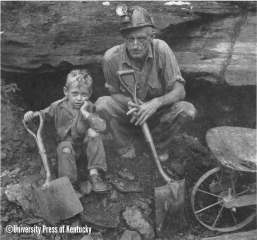 """In 1949, rounding a sharp curve in the road leading to Pippa Passes, Kentucky, my attention was drawn to a wisp of vapor that seemed to come from a hole in the mountainside which turned out to be a small-seam coal mine. Looking into the entry, I saw a flickering light about a hundred feet from the driftmouth and a voice called, """"Bet you want our picture!"""" The voice's owner could see a camera dangling from my neck. """"Be there in a minute,"""" the voice added, and presently a man wearing a carbide lamp atop his miner's cap appeared, followed by a tousle-headed boy, maybe eight years old. """"Name's Teach Slone and this boy is my son,"""" he said."""