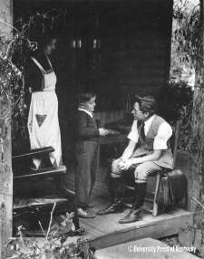 Nola Blair, a nurse of the Frontier Nursing Service, talks to a child she delivered on Munch Creek on the headwaters of the Kentucky River near Hyden, Kentucky [1941]. In the early days of the FNS, the nurses served an eight-hundred-square-mile area on horseback.