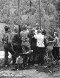 Recess time at Hindman Settlement School finds an eager group of youngsters at a well on the campus. [Hindman, Kentucky, 1959.]