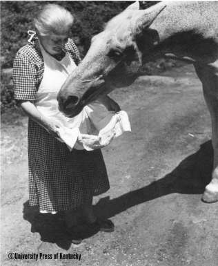 The late and beloved Mary Breckinridge, founder of the renowned Frontier Nursing Service in Kentucky's Cumberland Mountains, feeds her horse, Calico, from her apron.