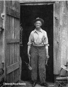 Newton Hylton at the door of his blacksmith shop, on a cliff overlooking Laurel Fork Creek.